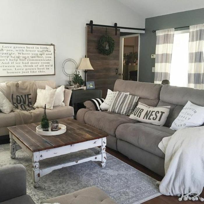 deco campagne chic, au charme industriel. table basse en bois, tapis et canapés gris, porte en bois rustique, panneau decoratif mural vintage