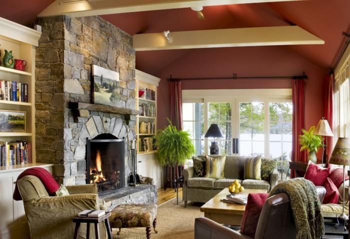 salon rustique avec une cheminee en pierre, mur couleur rouge, canapés et fauteuils, bibliothèque, table basse en bois, poutre apparente