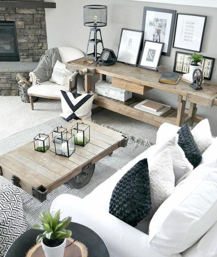 deco campagne chic rustique scandinave, une table en bois à roulettes, tapis gris, canapé blanc et coussins en gris et blanc, deco avec cadres, cheminée pierre,