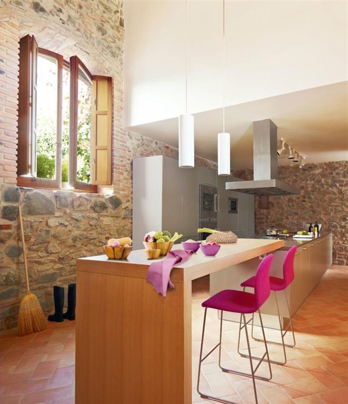 cuisine aménagée, chaises rose, cuisine en bois, fenêtres, mur en pierre, lampes blanches suspendues, mur blanc