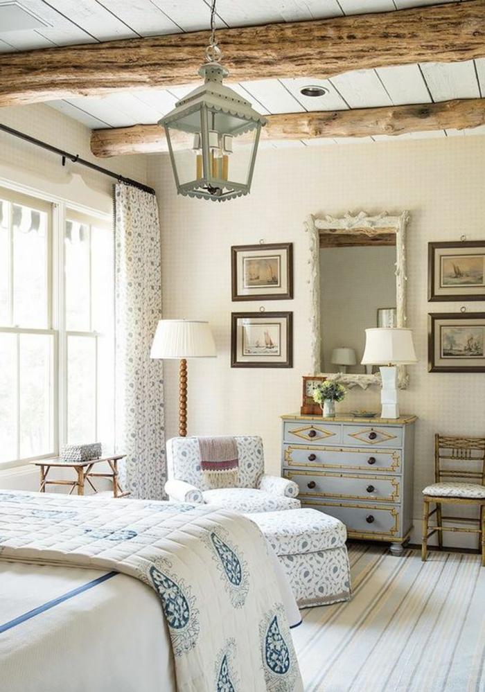 deco chambre a coucher style campagne chic, poutres apparentes, commode vintage bleu pastel, linge de lit blanc et bleu, suspension lanterne, tapis à rayures, canapé, tabouret et rideaux à motifs floraux