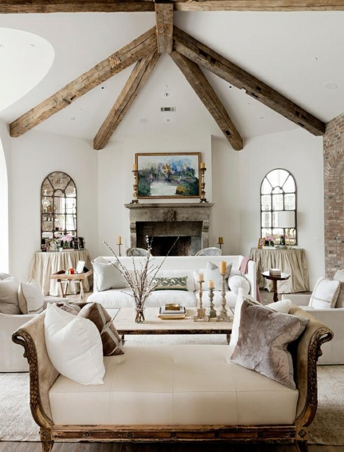 deco campagne chic rustique, poutre apparente, canapé et fauteuils blancs, des baies vitrées, cheminee en pierre, deco chandeliers, chaise longue vintage