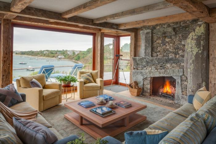 deco campagne chic avec cheminee rustique en pierre, table basse en bois, canapé multicolore avec coussins, fauteuil jaune, poutre apparente, grande fenetre, vue sur la mer