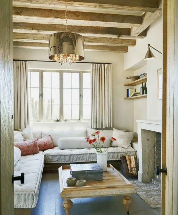 deco campagne chic, cheminee en pierre, table basse en bois clair vintage, canapés blanc, coussins rose, poutre en pierre, etagere murale en bois, parquet en bois gris, suspension design