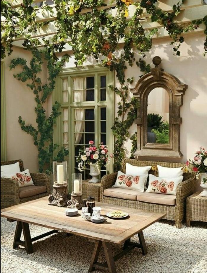 deco exterieur campagne chic, table basse en bois, fauteuil et canapé en rotin, tapis gris, coussins liberty et decoration florale