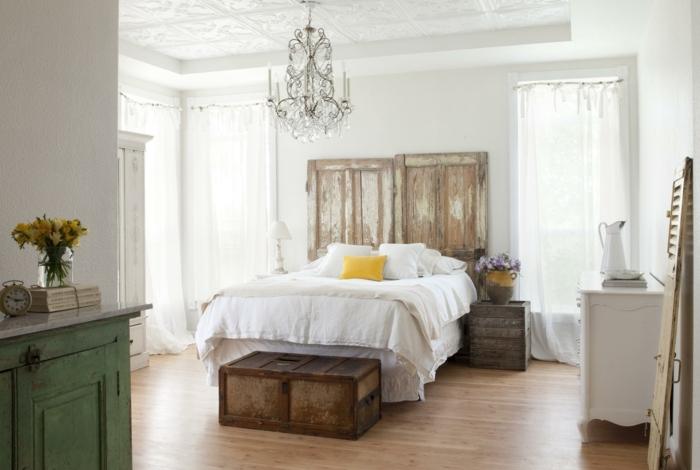 idée deco campagne chambre à coucher adulte, linge de lit, bout de lit coffre metallique, table de nuit cagette bois, portes en bois décoratives usées, lustre baroque