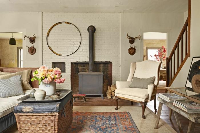 table fabriqué à partir de coffret en rotin, canapé en cuir, cheminee vintage, fauteuil retro, tapis vintage oriental, decoration bois de cerf, salon rustique