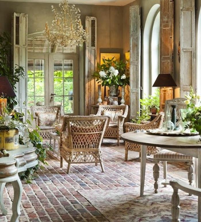 deco campagne chic, revêtement sol en briques, chaises en rotin, mur couleur grise, decoration florale, coin repas, table ronde et chaises en bois, lustre fleuri