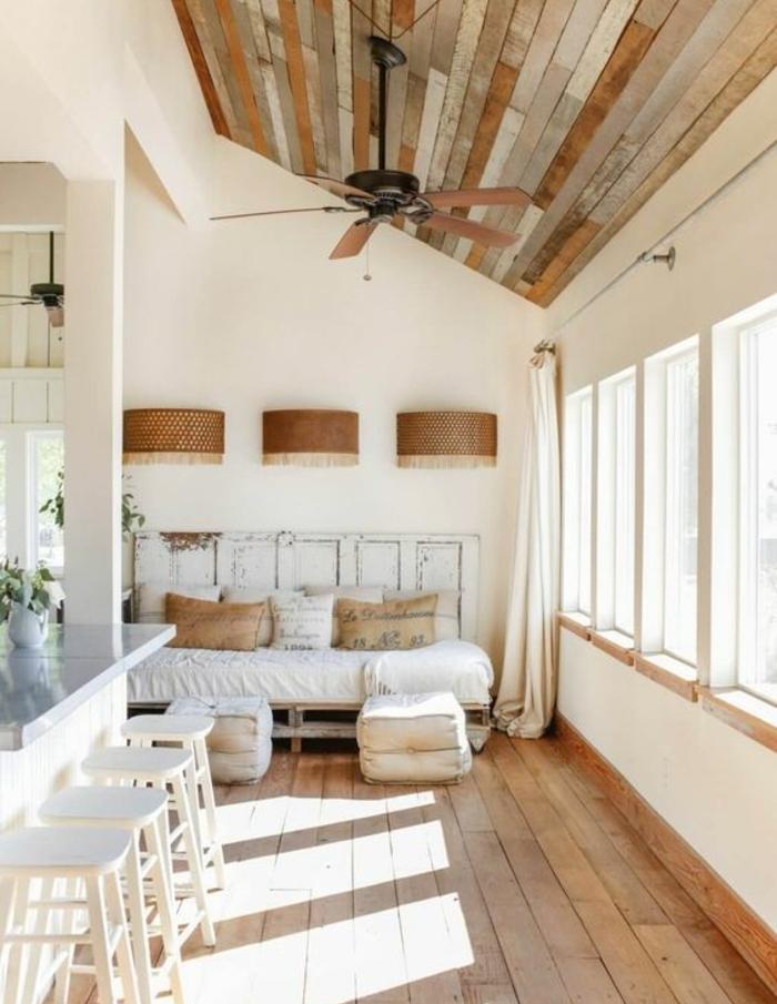 idée intérieur campagne chic, canapé en palette vinatage, coussins blancs et marron, plafond de planches en bois, tabourets et bar blancs
