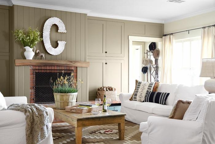 table basse en bois brut, canapé et fauteuils blancs, lettre decorative mural, cheminee, tapis marron à motifs, coussins multicolores, deco contemporaine rustique