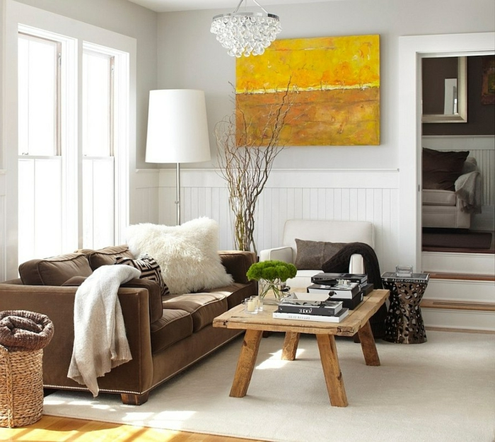 deco contemporaine salon avec une table basse rustique charme scandinave, canapé marron, fauteuil blanc, deco mural tableau jaune, suspension design, tapis blanc cassé