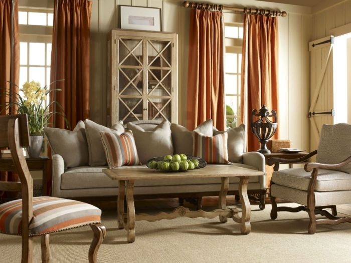 tapis, canapé et fauteuil gris, chaise à en bois à rayures, tentures orange, table basse en bois vintage, lambris, buffet vintage, deco campagne chic