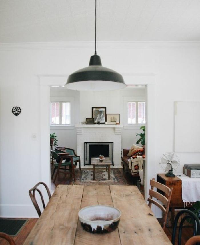 salle à manger qui s ouvre sur un salon campagne chic, table en bois brut, chaises en bois, cheminée, canapé et chaises, tapis oriental, suspension industrielle