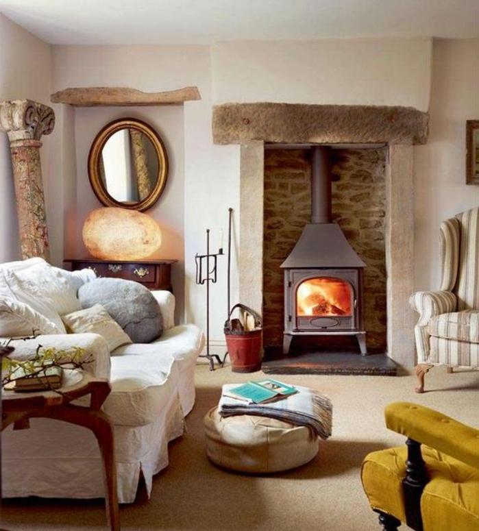 deco sejour campagne chic, canapé blanc, coussins decoratifs, pouf, cheminée romantique pierre, miroir rond, colonen grecque, fauteuil jaune moutarde