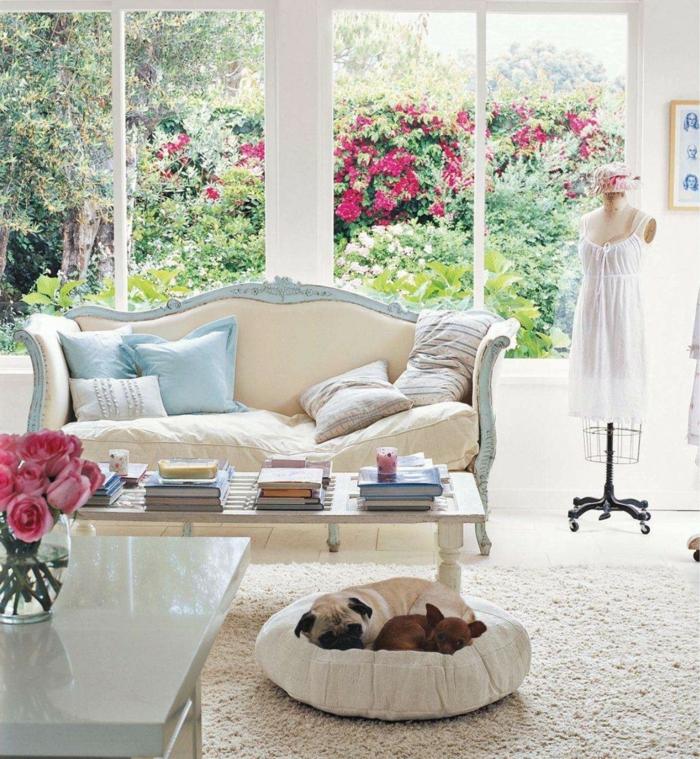 deco campagne chic salon, canapé vintage, coussins décoratifs, table basse blanche en bois, lit chien, tapis blanc, grandes fenêtres
