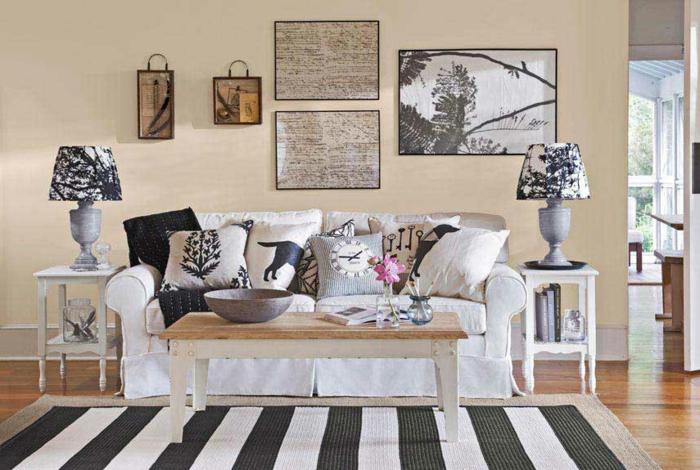 canapé blanc, table basse en bois, tapis à rayures, noir et blanc, coussins en gris, blanc et noir, mur couleur beige, parquet clair, decoration murale