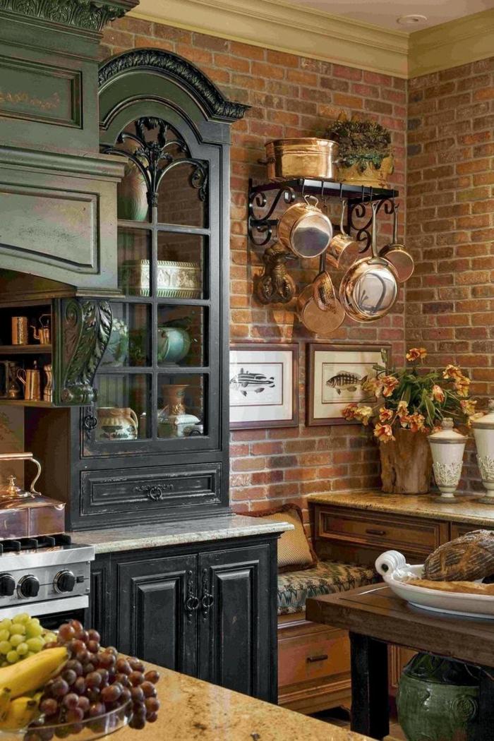 cuisine aménagée, bol à fruits, peinture avec cadre en bois, murs en briques, étagère murale en fer forgé, cuisine en bois