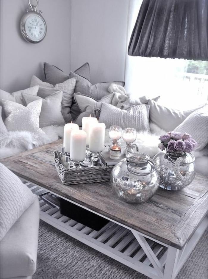 deco campagne chic en gris, table basse en bois brut, bougies, vases de fleurs, coussins blancs et gris, tapis gris, horloge vintage