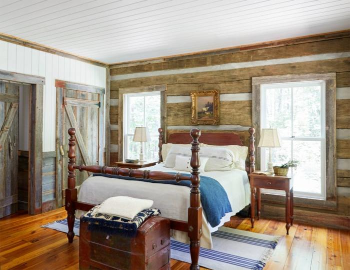 chambre a coucher campagne chic, lit en bois vintage, bout de lit, coffre vintage, mur en poutres de bois burt, portes en bois usé, paquet marron