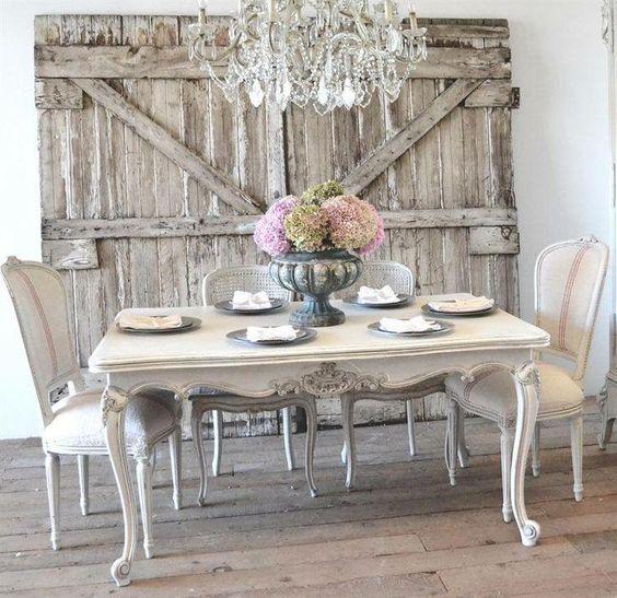 idee deco campagne française, table en bois et chaises blanches, portes en poutres de bois, lustre vintage, centre de table floral