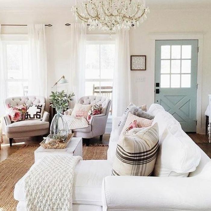 deco sejour campagne chic, canapé blanc, coussins motif liberty, plaid au crochet, canpés couleur blanc cassé, porte bleu pastel, lustre baroque