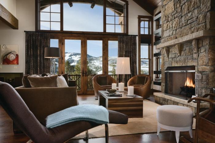 salon rustique maison dans la montagne, cheminee en pierre, table basse en bois, fauteuils en cuir, canapé marron, chaise longue en cuir, tapis couleur fauve, grandes fenêtres