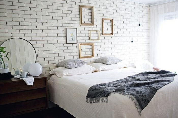 mur de cadres rectangulaires et dessin encadré, mur en briques, table de nuit en bois, linge de lit blanc et gris, decoration de chambre scandinave