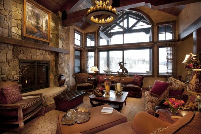 deco contemporaine dans un style rustique, canapé en cuir, fauteuil marron, chaise en bois, cheminée en pierre, lustre avec des bougies, tapis vintage, table basse en bois, vue paysage montagneux