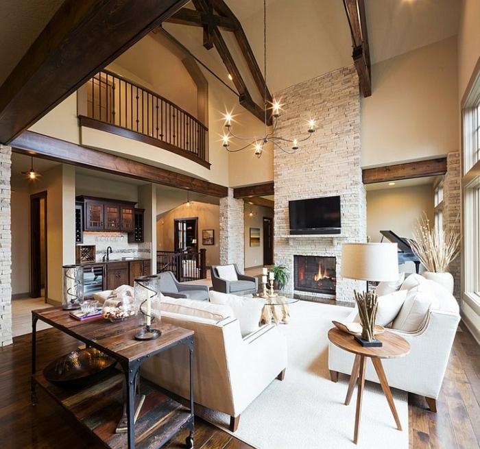 deco contemporaine, canapés et tapis blanc cassé, table en verre, cheminée en briques, suspension elegante, parquet en bois marron, fauteuils gris