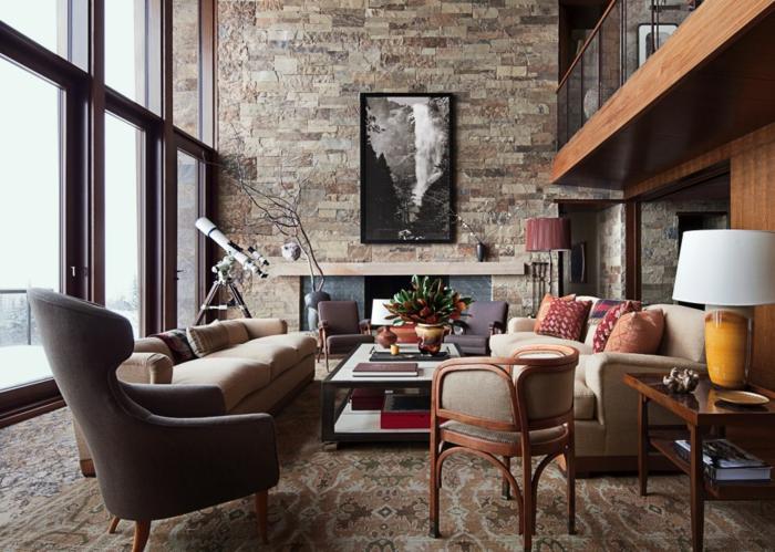 mur en pierre, canapé fauve, tapis oriental à motifs, fauteuil gris, table basse en métal, coussins multicolores, cheminée, grosses fenêtres