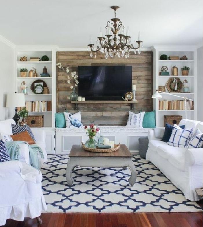 deco campagne chic avec des canapés blancs, coussins multicolores, parquet marron, mur-d-accent en planches de bois, etageres avec decoration, lustre elegant, tapis blanc à motifs bleus