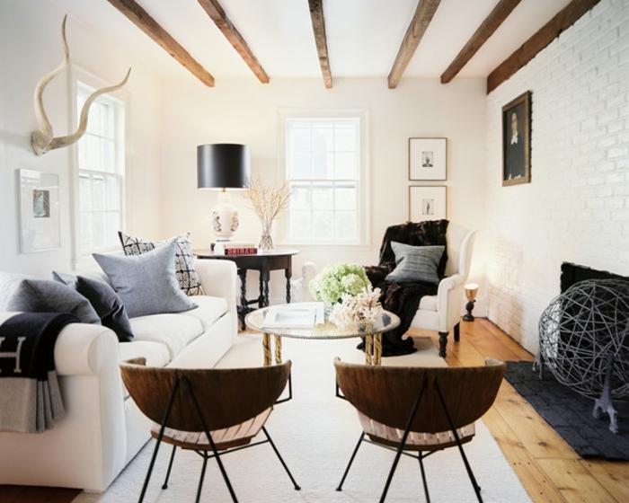 deo campagne chic rustique, chaises en bois, canapé blanc, coussins gris, table en verre et metal ronde, tapis blanc, cheminee, mur d accent en briques blanches, poutre apparente, deco murale en bois de cerf