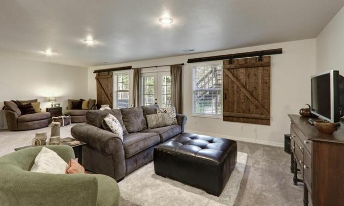 meuble tv en bois vintage, canapé et fauteuils gris, tapis blanc cassé, volets de fenêtre, salon rustique, mur couleur blanche