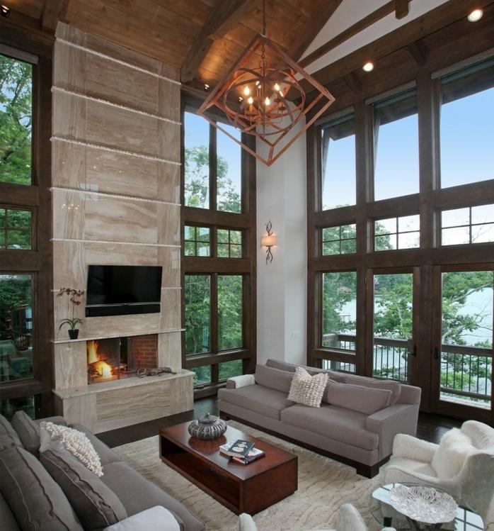 deco campagne chic rustique, toiture boiserie, canapés gris, fauteuils blancs, cheminee moderne, table basse en bois, suspension originale, beaucoup de fenetres