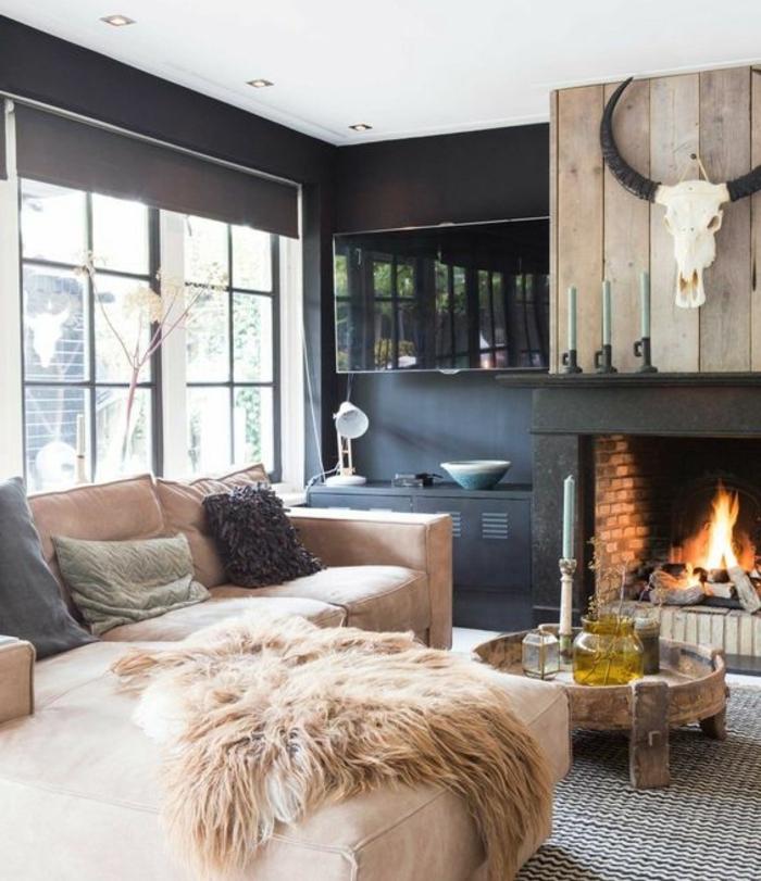 salon rustique, tapis en noir et blanc, canapé d angle fauve, table basse en bois, cheminee romantique, murs couelur noire et plafond en blanc, deco murale trophée, boiserie