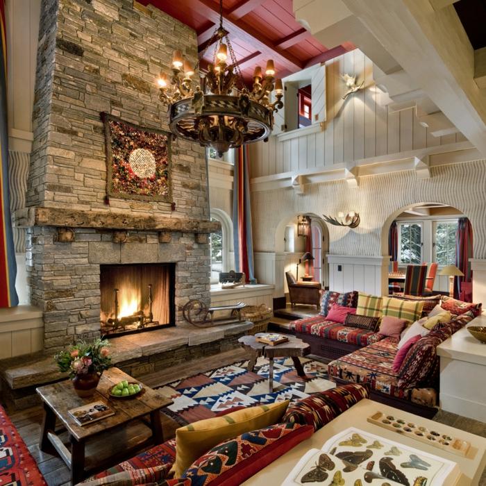 deco contemporaine rustique bohème, salon avec cheminée en pierre, tapis à motifs amérindiens, canapé ethnique avec coussins multicolores, table basse en bois brut, lustre original