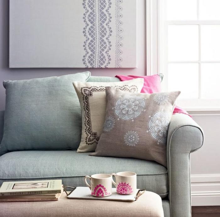 motifs deco dentelle, coussin beige, marron et gris, canapé gris, table basse et mugs personnalisés, livres
