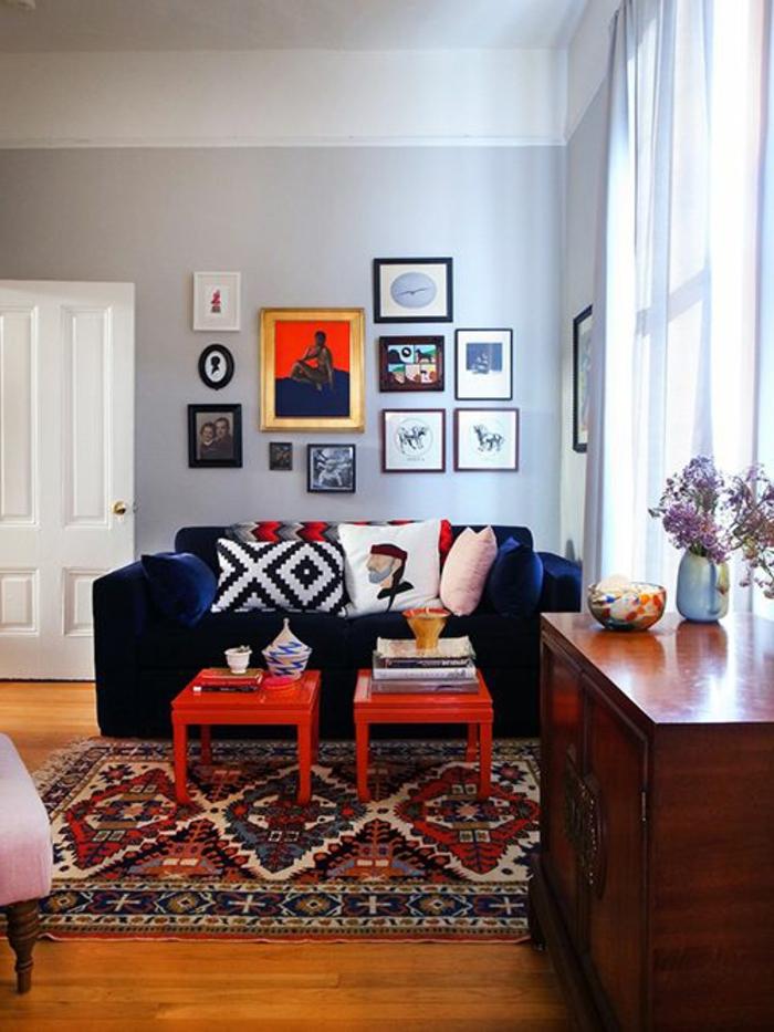 deco gris blanc, coussins géométriques, tables basses oranges, plusieurs tableaux encadrés