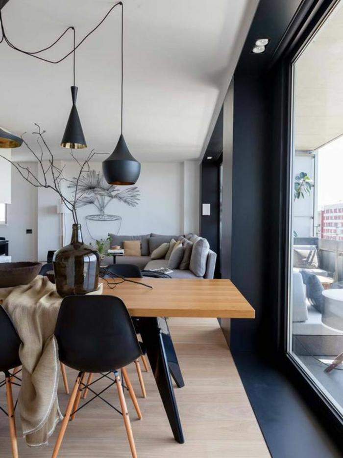 couleur gris perle, salon lumineux, fenêtres du plafond au sol, grande table en bois et suspensions noires