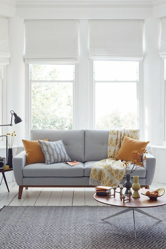 deco gris blanc, sol en planches blanches, coussins, table ronde en bois, salon lumineux