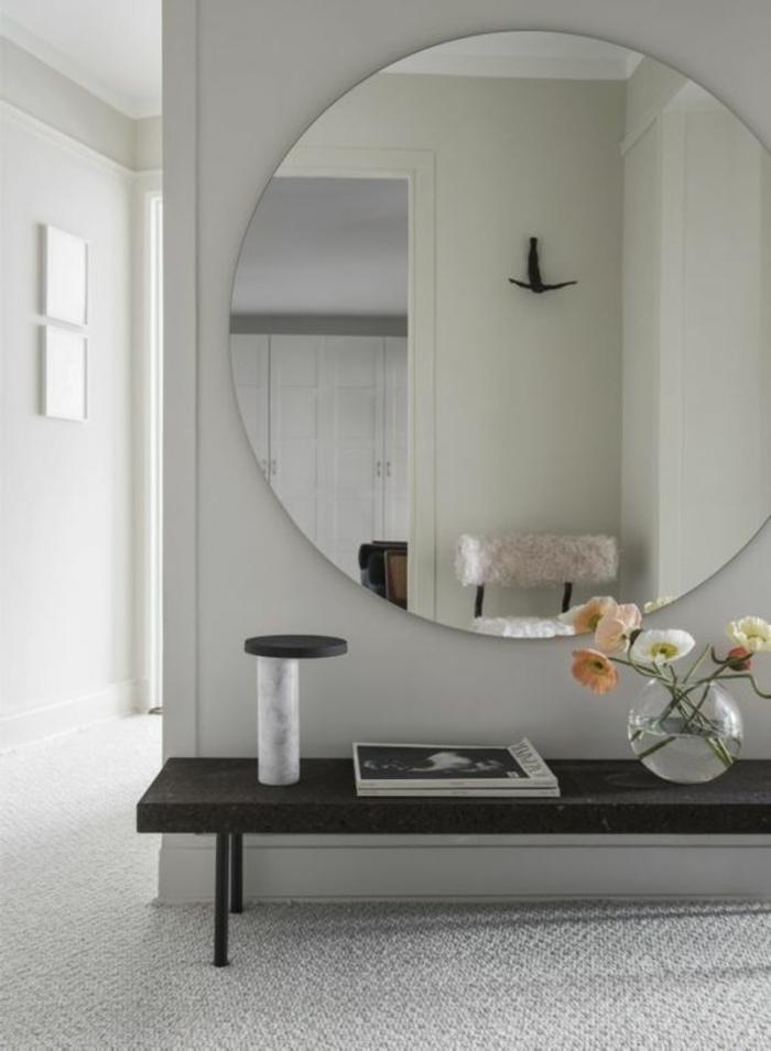 hall d'entrée maison avec grand miroir tout rond et table noire basse sur fond blanc