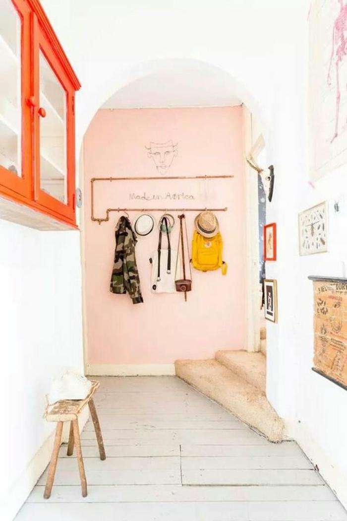 hall entrée maison avec un meuble orange et un mur rose avec des escaliers en rose
