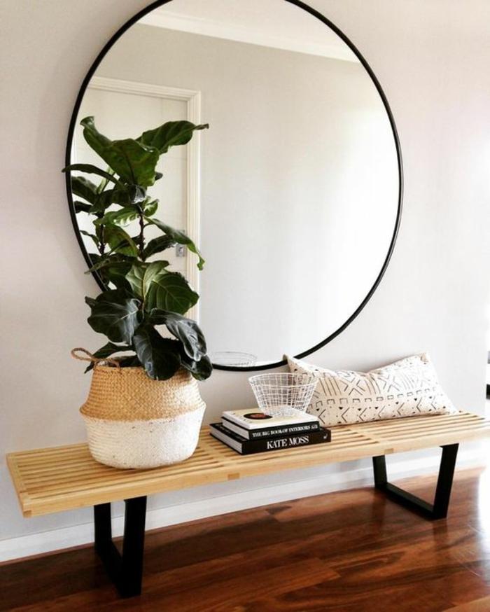 decoration hall de maison avec grand miroir tout rond et banc avec coussin en bois clair et pieds métalliques en noir