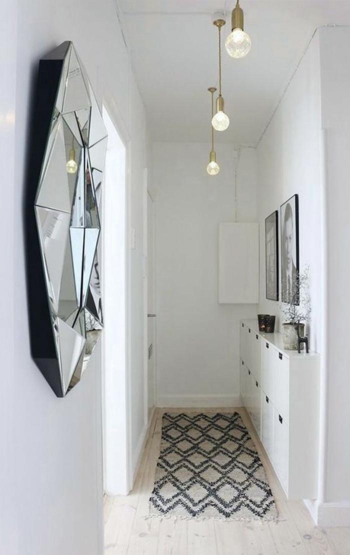 hall d'entrée maison espace long et étroit avec miroir rond à la surface irrégulière et 3 luminaires ampoules