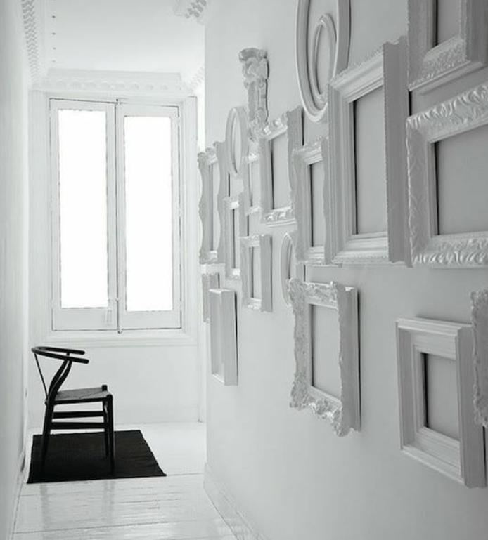exemple de decoration monochrome, composée de plusieurs cadres photo sur un mur tout en blanc, tapis et chaises noirs, parquet blanc, fenêtre, idée comment décorer un mur blanc