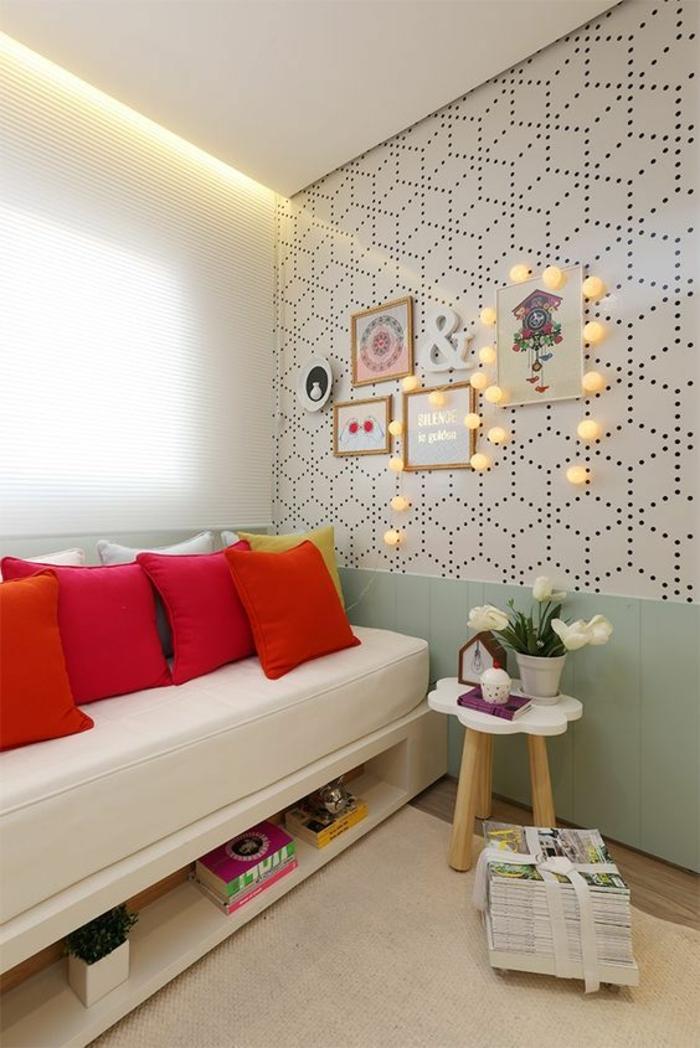 mur de cadres, coussins rouges, canapé blanc, plafond suspendu, table en bois, livres, stores blancs
