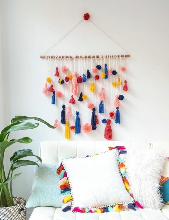 deco murale a faire soi meme, pompons ronds et pompons a franges multicolores suspendus a un baton en bois, activité manuelle adulte, decoration style boheme, multicolore