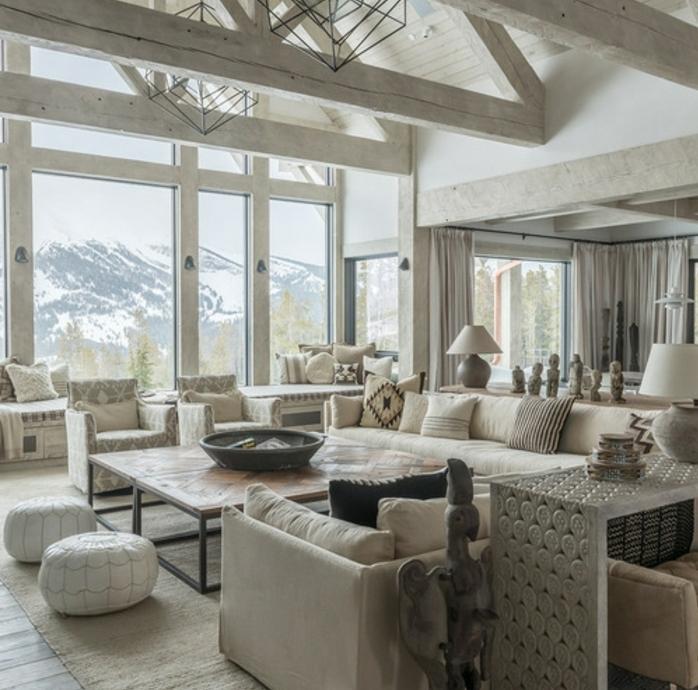 salon rustique blanc, tapis , canapés blanc cassé, poufs blancs, table en bois et métal, fauteuils blanc et gris, poutre apparente, vue sur la montage, grandes fenêtres