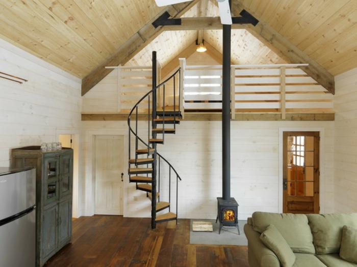 salon rustique sous comble, cheminee, parquet en bois usé, buffet patné, canapé vert pistache, escalier helicoidal, maison ossature bois