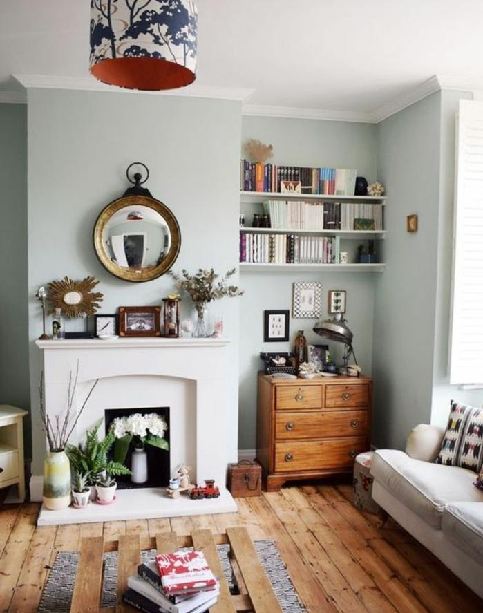 exemple de deco campagne dans le salon, parquet bois brut, canapé gris et blanc, table en palette de bois, cheminée, mur couleur vert pastel, etagere rangement livres